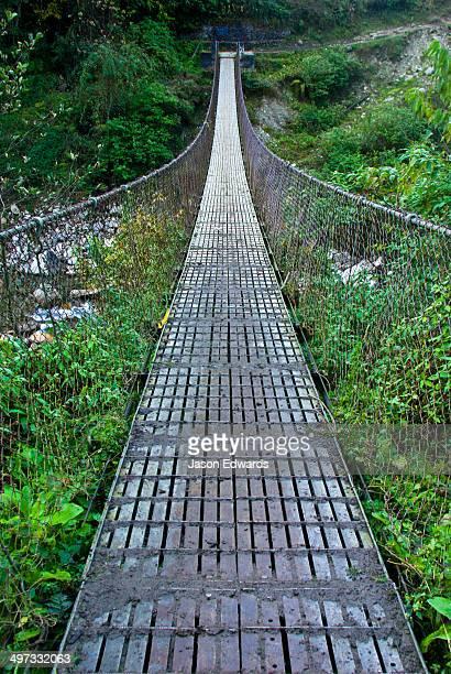 The metal planks of a suspension bridge cross between mountain valley walls in the Himalaya.