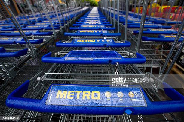 The Metro logo sit on shopping cart handles outside a Metro AG Cash Carry wholesale store in Duesseldorf Germany on Tuesday April 5 2016 German...