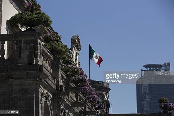 The Mexican flag flies above the Chapultepec Castle which houses Mexico's National Museum of History as a gardener works on a flowered balcony in...