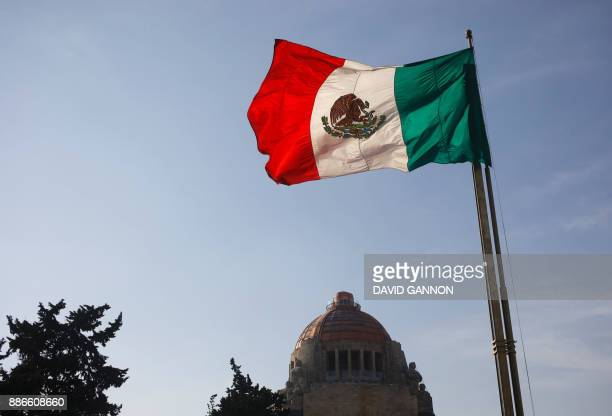 The Mexican flag flutters in the wind in front of the Monument to the Revolution in Mexico City on December 5 2017 The Monument to the Revolution...