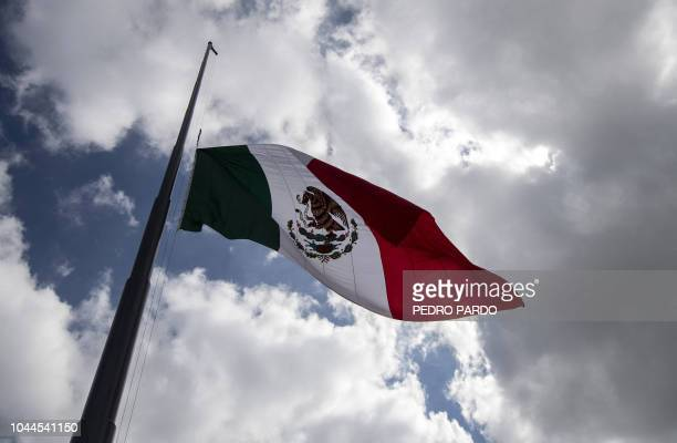 The Mexican flag is seen at half mast on the 50th anniversary of the 1968 Tlatelolco student massacre at the Zocalo square in Mexico City on October...