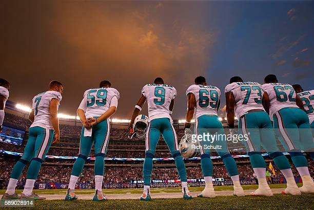 The Miami Dolphins line up for the national anthem as the sun sets before an NFL preseason game against the New York Giants at MetLife Stadium on...