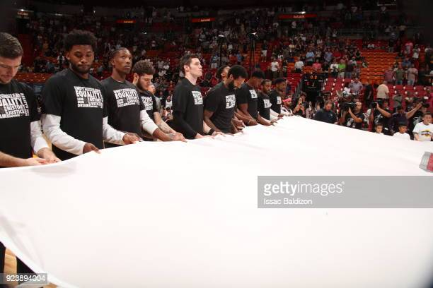the Miami Heat hold the Marjory Stoneman Douglas HS flag prior to the game against the Memphis Grizzlies on February 24 2018 at American Airlines...