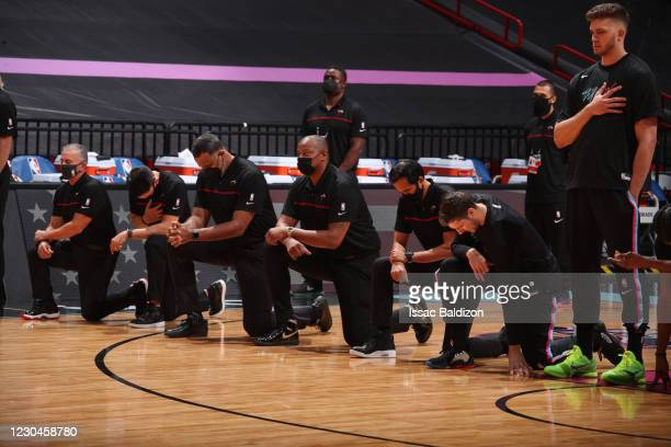 The Miami Heat players and coaching staff look on during the national anthem before the game against the Boston Celtics on January 6, 2021 at...