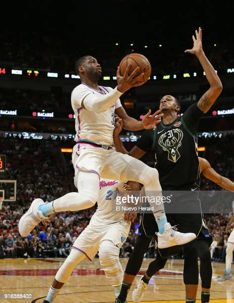 The Miami Heat's Dwyane Wade goes to the basket against the Milwaukee Bucks' John Henson during the second quarter at the AmericanAirlines Arena in...