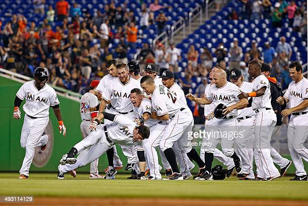 The Miami Marlins celebrate after Christian Yelich hit a walkoff single during the ninth inning of the game against the Philadelphia Phillies at...