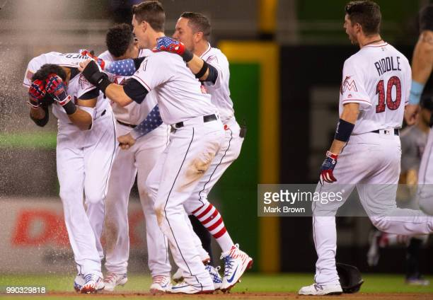The Miami Marlins celebrate the walk off single by Yadiel Rivera in the tenth inning against the Tampa Bay Rays at Marlins Park on July 2, 2018 in...