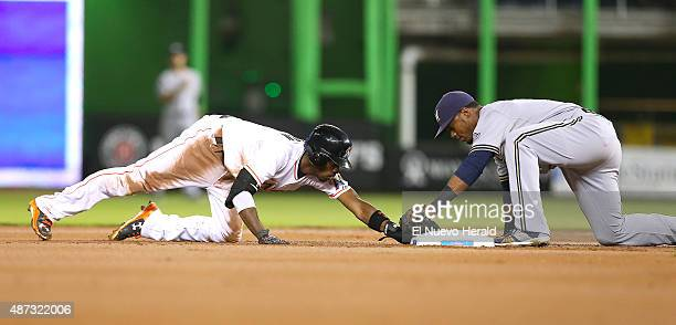 The Miami Marlins' Dee Gordon left steals second base as Milwaukee Brewers shortstop Jean Segura is unable to tag him out in the first inning on...
