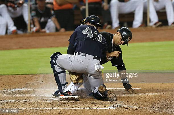 The Miami Marlins' Martin Prado slides into home as New York Yankees catcher Austin Romine tags him out during the sixth inning of exhibition play on...