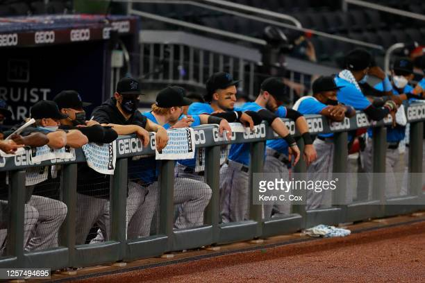 The Miami Marlins stand in the dugout during the seventh inning of an exhibition game against the Atlanta Braves at Truist Park on July 21 2020 in...