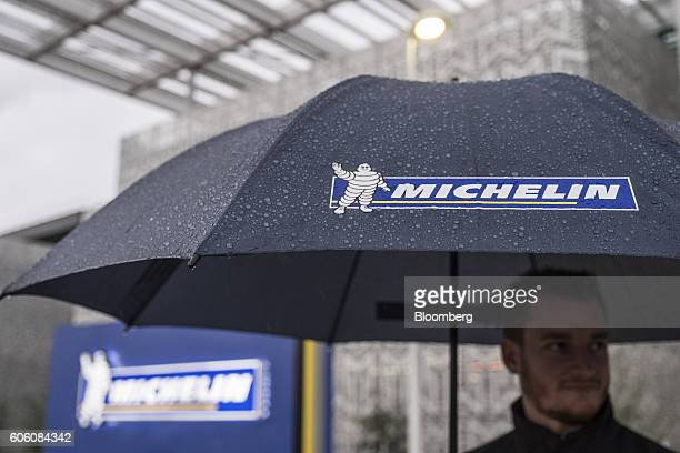 The Michelin Cie Bibendum mascot also known as the Michelin Man sits on an employee's umbrella as rain falls outside the new Michelin research and...