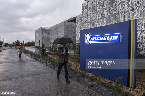 The Michelin Cie Bibendum mascot also known as the Michelin Man sits on a sign as rain falls outside the new Michelin research and development campus...