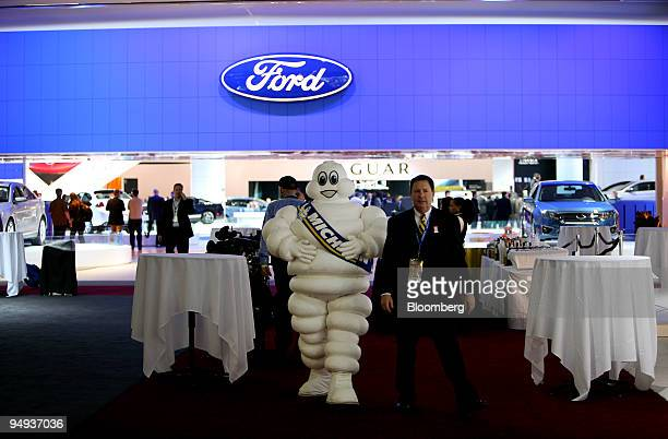 The Michelin Man representing Michelin Cie tire company walks near the Ford Motor Co booth at the 2009 North American International Auto Show in...