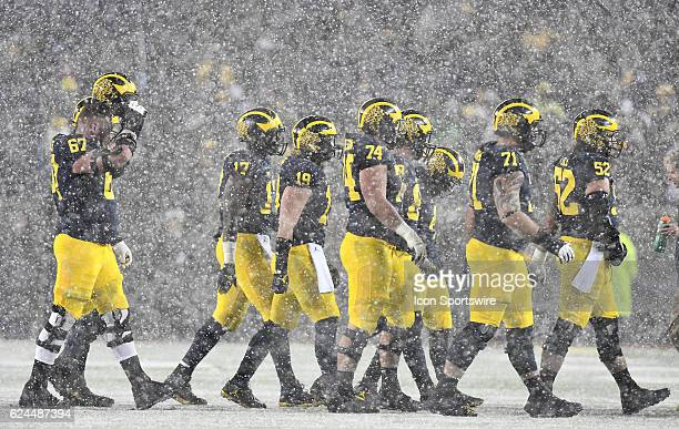 The Michigan offensive line heads for the sidelines for a timeout as a snow squall passes through Ann Arbor in the fourth quarter of the Michigan...