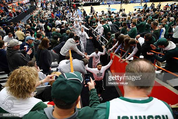The Michigan State Spartans high five fans prior to their game against the Louisville Cardinals during the East Regional Final of the 2015 NCAA Men's...