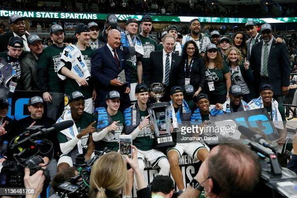 The Michigan State Spartans pose for photos after beating the Michigan Wolverines 65-60 in the championship game of the Big Ten Basketball Tournament...