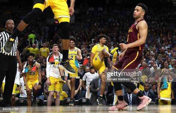 The Michigan Wolverines bench reacts after a dunk late in the second half against the Loyola Ramblers during the 2018 NCAA Men's Final Four Semifinal...