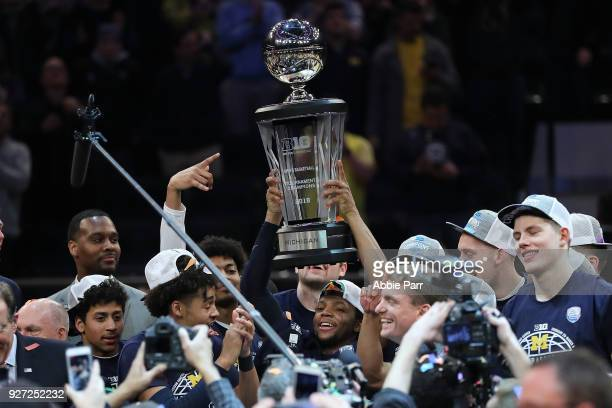 The Michigan Wolverines celebrate after defeating the Purdue Boilermakers 7566 during the championship game of the Big 10 Basketball Tournament at...