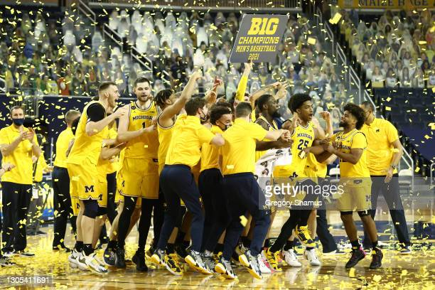The Michigan Wolverines celebrate their 2021 Big Ten Championship after defeating the Michigan State Spartans 69-50 at Crisler Arena on March 04,...