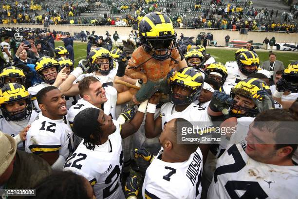 The Michigan Wolverines celebrate winning the Paul Bunyan trophy with a 21-7 win over the Michigan State Spartans at Spartan Stadium on October 20,...