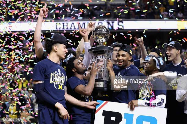 The Michigan Wolverines celebrate with the trophy after the Wolverines defeated the Wisconsin Badgers to win the Big Ten Basketball Tournament...