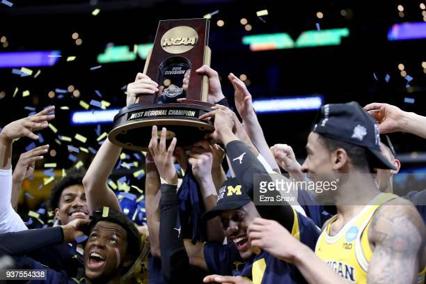 The Michigan Wolverines celebrate with the West Regional trophy after their 58-54 victory against the Florida State Seminoles in the 2018 NCAA Men's...