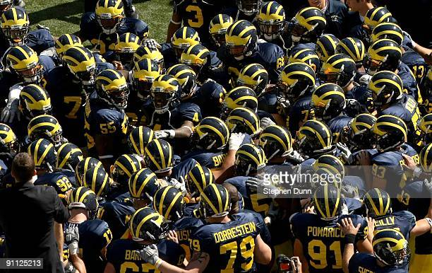 The Michigan Wolverines huddles on the field before the game against the Eastern Michigan Eagles at Michigan Stadium on September 19, 2009 in Ann...