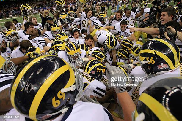 The Michigan Wolverines pile on kicker Brendan Gibbons after Gibbons kicked a successful 37-yard game-winning field goal in overtime against the...