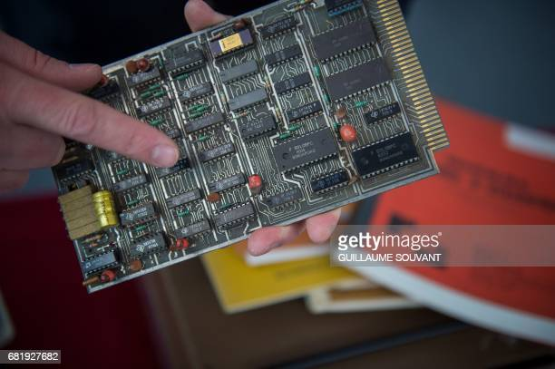 The microprocessor's card of the first microcomputer named 'Micral N' is shown by the auctioneer on May 11 2017 in Tours ahead of an auction next...