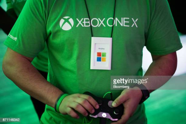 The Microsoft Corp flagship store employee plays on an Xbox Developer Kit version of the Xbox One X game console during the global launch event in...