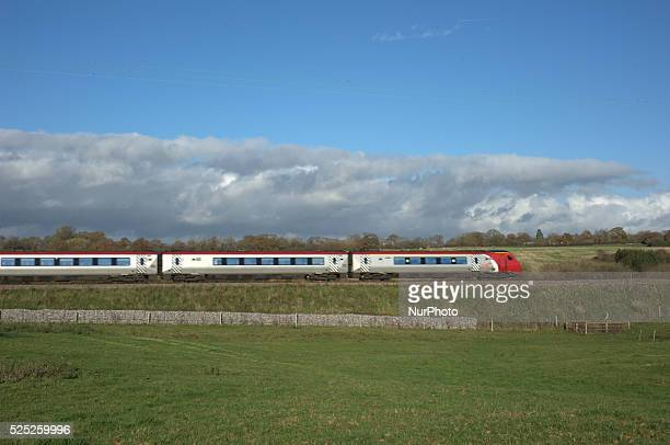 The midafternoon sun glinting off a Virgin Voyager travelling from Chester to Crewe as sunlight reflects on to the grass of the field