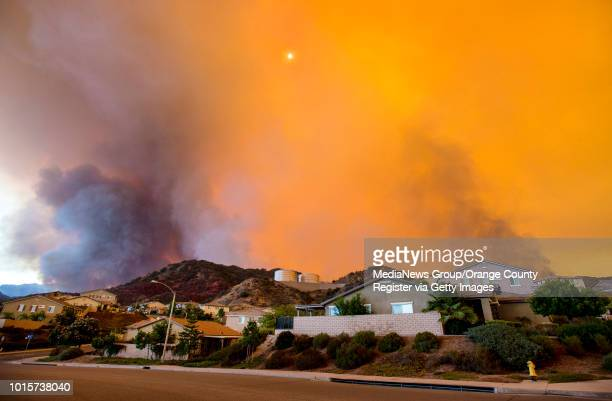 The midafternoon sun is nearly blocked out along McVicker Canyon Park Road in Lake Elsinore as the Holy fire burns near homes on Wednesday afternoon...