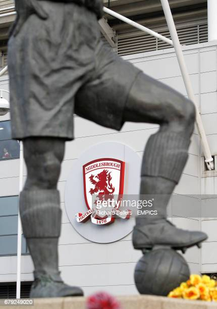 The Middlesbrough FC club crest seen through the legs of the George Hardwick statue at Riverside Lane