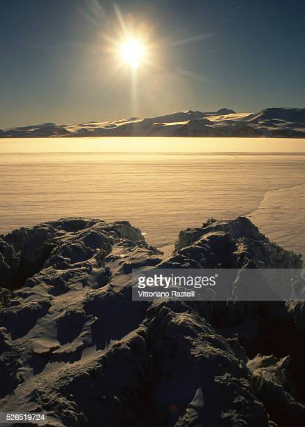 The midnight sun shines over the Ross Sea Antarctica seen from a helicopter