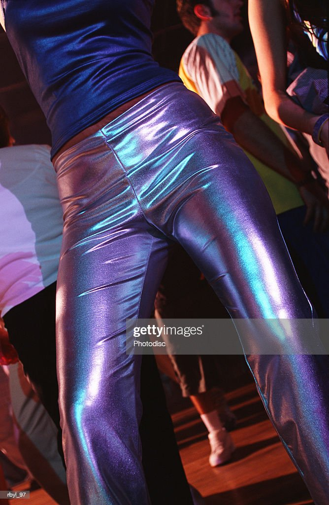 the mid-section of a girl in tight silver vinyl pants and a blue shirt dancing in a nightclub : Foto de stock