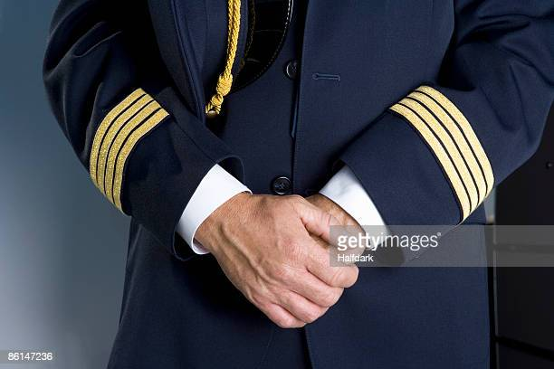 the midsection of a pilot standing with his hands clasped - aviation hat stock photos and pictures