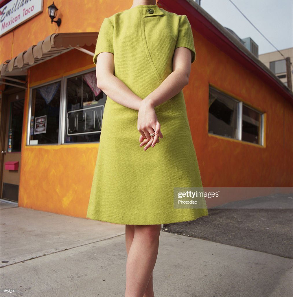 the mid-section of a young women in a green dress standing on a street corner with her hands together in a standing pose : Foto de stock
