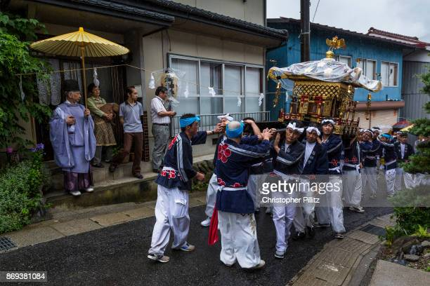 The Mikoshi is carried through the village of Kiso Mura as part of the Summer festival parade Here been ovesrlloked by Kazufumi Okutani 71 the senior...