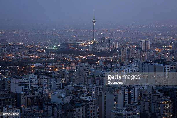 The Milad Tower top center also known as the Tehran Tower stands illuminated beyond residential and commercial properties on the city skyline i in...