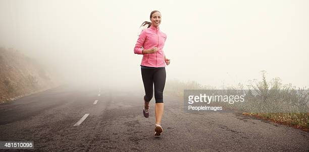 the miles are rolling away behind her - jogging stock photos and pictures