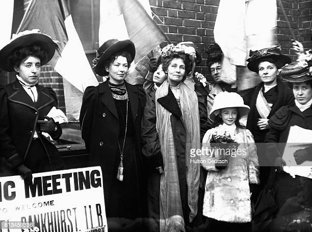 The militant campaigner for female suffrage Emmeline Pankhurst and one of her daughters are welcomed to a meeting of fellow suffragettes with banners...