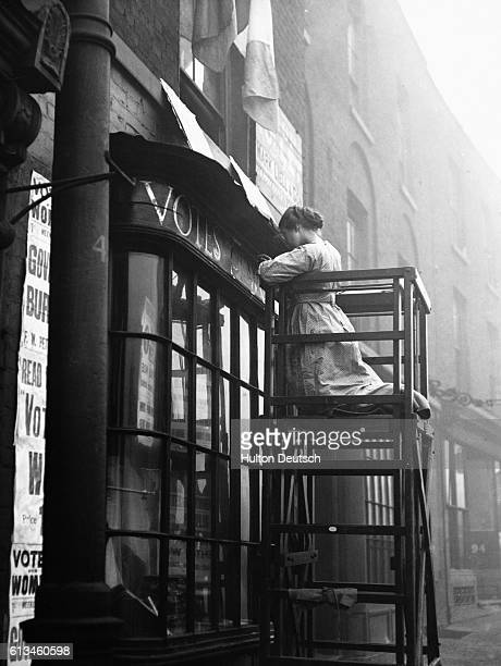 The militant suffragette Sylvia Pankhurst at work painting 'votes for women' on the shop front of the Women's Social Defence League in Bow Road