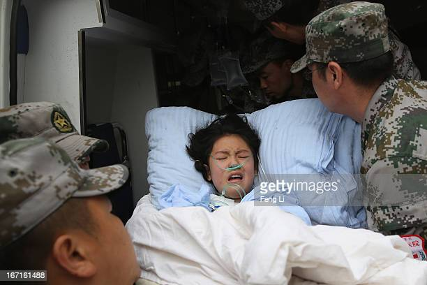 The military medical officers carry a patient to an ambulance at the hospital on April 22 2013 in Lushan of Ya An China A magnitude 7 earthquake hit...