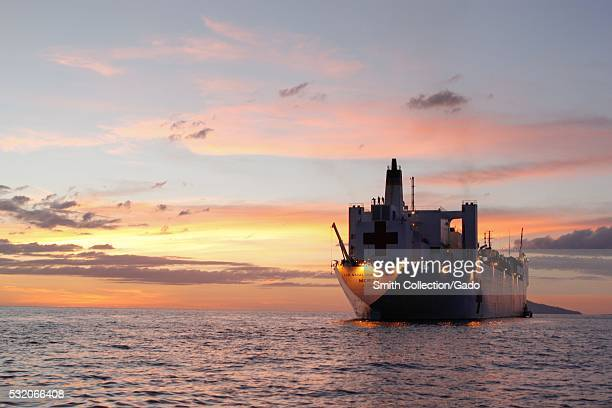 The Military Sealift Command hospital ship USNS Mercy TAH19 is underway off the coast of Manado Bay at sunset after the opening ceremony for Pacific...