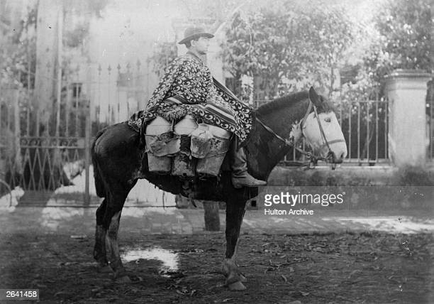 The milkman wearing a poncho delivers milk from small churns carried either side of the horse