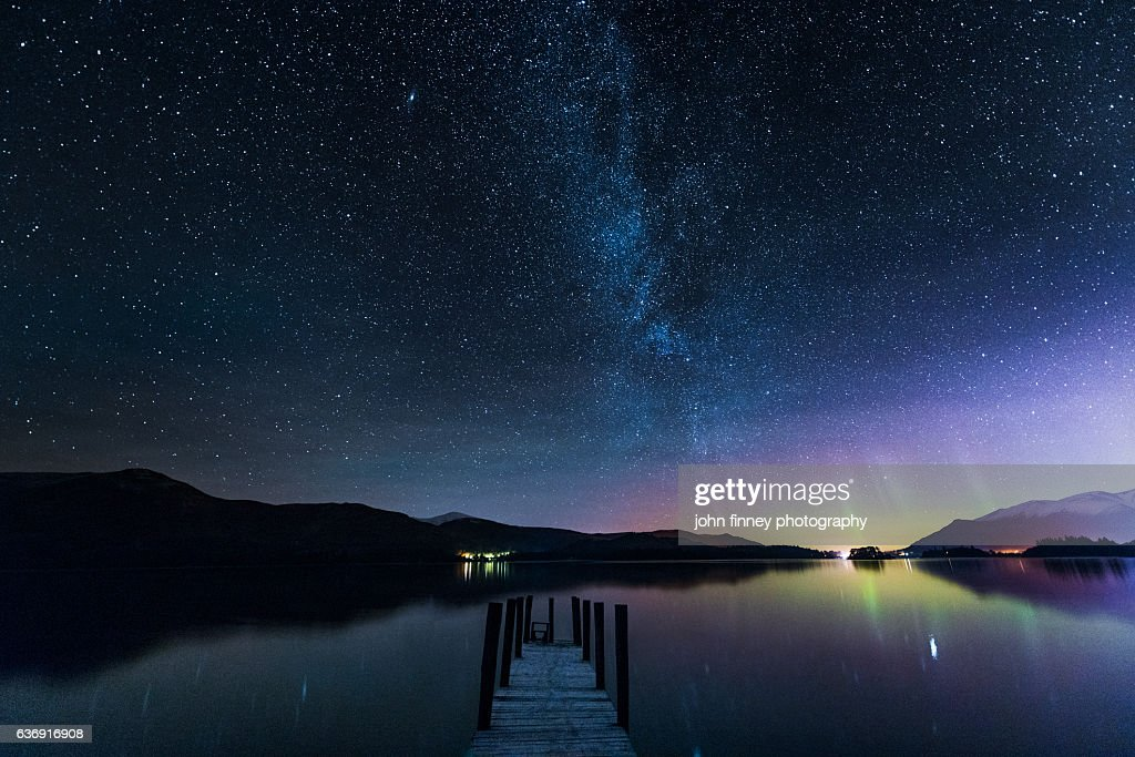 The Milky Way and Aurora Borealis from a jetty over Derwent water. English Lake District. UK : Stock Photo