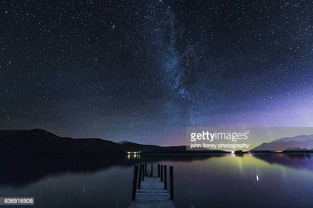 the milky way and aurora borealis from a jetty over derwent water. english lake district. uk - lake district stockfoto's en -beelden