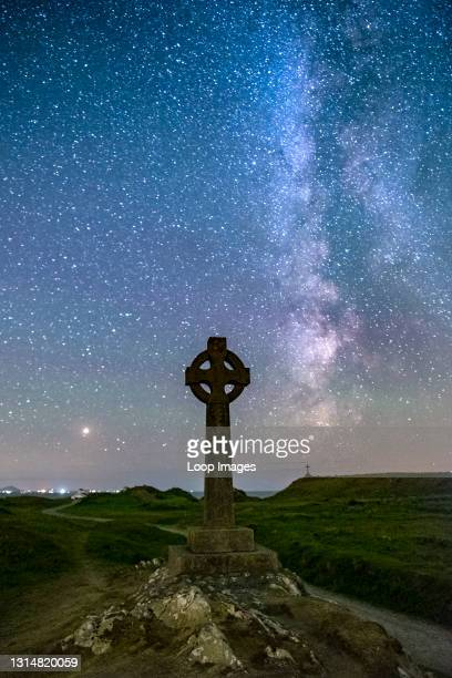 The Milky Way and night sky over the Celtic Cross at Llanddwyn Island on Anglesey.