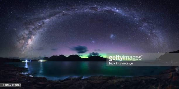 the milky way arches over the hazards while the aurora australis glows beyond, freycinet national park, tasmania, australia - aurora australis stock pictures, royalty-free photos & images