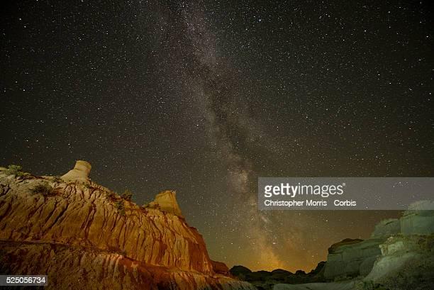 The Milky Way galaxy appears in the dark night sky over hoodoos in the Alberta Badlands at Dinosaur Provincial Park
